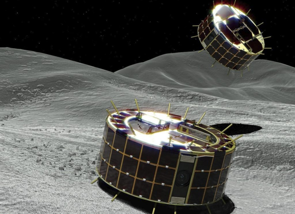 This computer graphic image provided by the Japan Aerospace Exploration Agency shows two drum-shaped and solar-powered Minerva-II-1 rovers that were released on an asteroid on Friday
