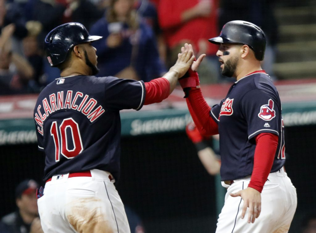 Cleveland's Edwin Encarnacion, left, and Yonder Alonso celebrate after scoring on a double by Melky Cabrera in the fourth inning Sunday night against the Boston Red Sox. The Indians won in 11 innings, 4-3.
