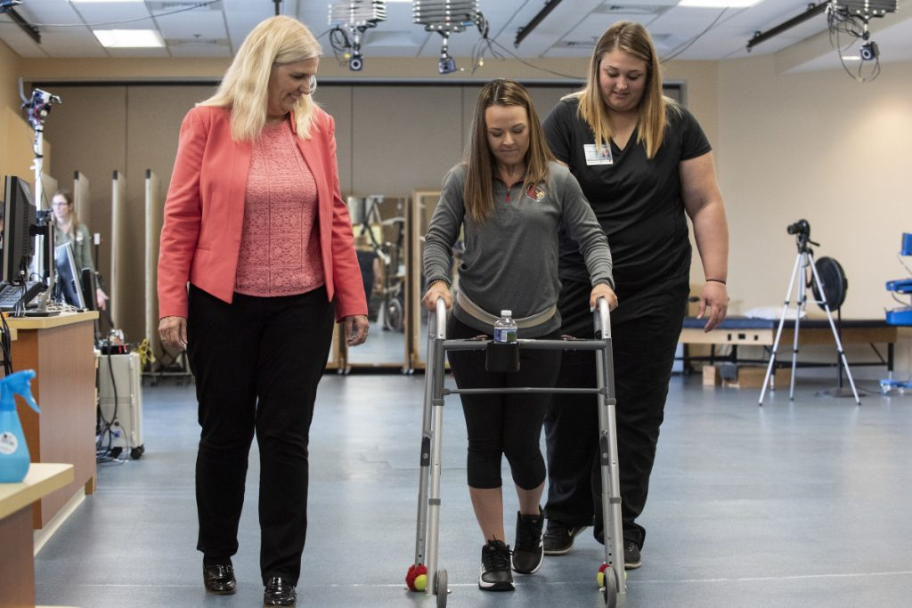 "In this May 22, 2018 photo provided by the University of Louisville, Professor Susan Harkema watches as Kelly Thomas of Lecanto, Fla., practices walking with the help of a walker. ""Recovery can happen if you have the right circumstances,"" says Harkema, who co-authored a report on the use of electrical implants to stimulate the spinal cord. (Tom Fougerousse/University of Louisville via AP)"