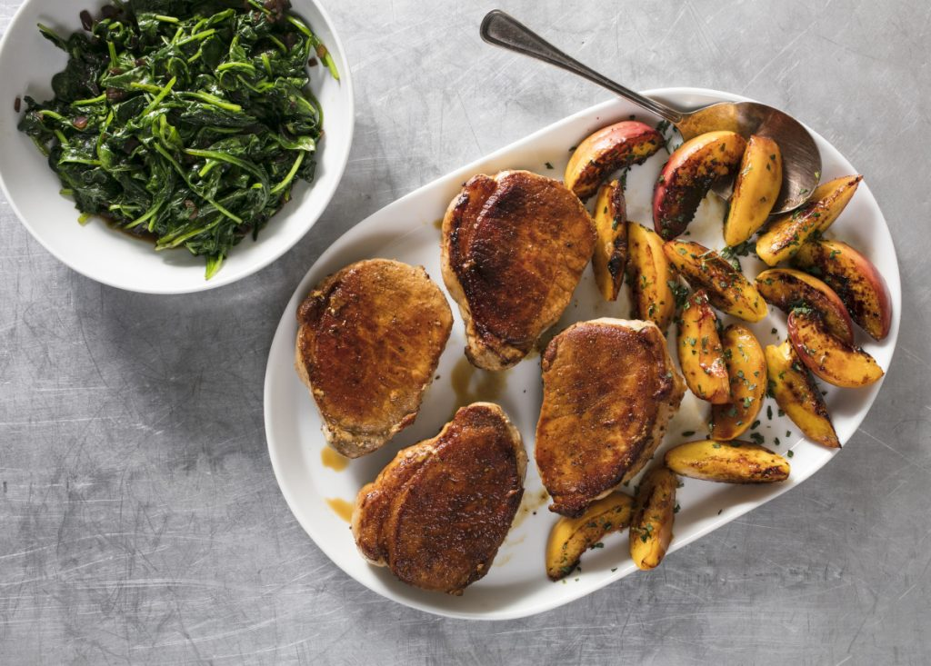 Pan-Seared Thick-Cut Boneless Pork Chops with Peaches and Spinach.