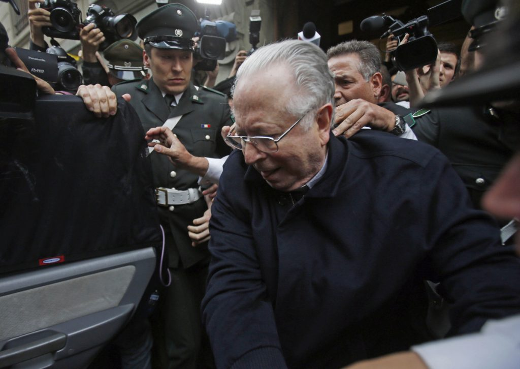 The Rev. Fernando Karadima is escorted from court after testifying in a case that three of his victims brought against the country's Catholic Church in Santiago, Chile, in 2015.