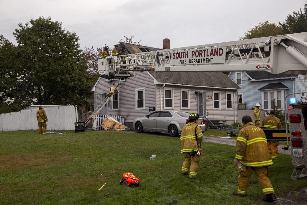 Firefighters finish putting out a fire in the second floor of a single family home at 12 Calais Street on Tuesday morning. South Portland Fire Chief James Wilson said the fire most likely started from an electrical problem, but they can't be certain until later. Both occupants of the home and their dogs were awake when the fire started and safely evacuated.