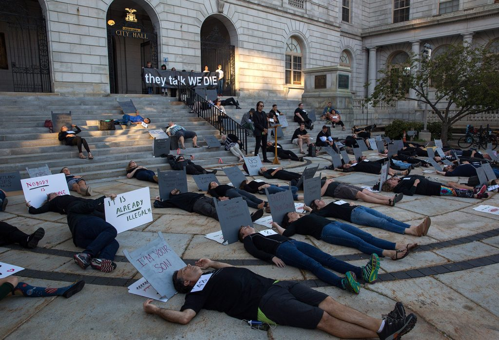 "A group of 57 people lay on the ground outside Portland City Hall on Friday for an overdose prevention ""die in."" The 57 people symbolized the 57 opioid overdose deaths in Portland last year."