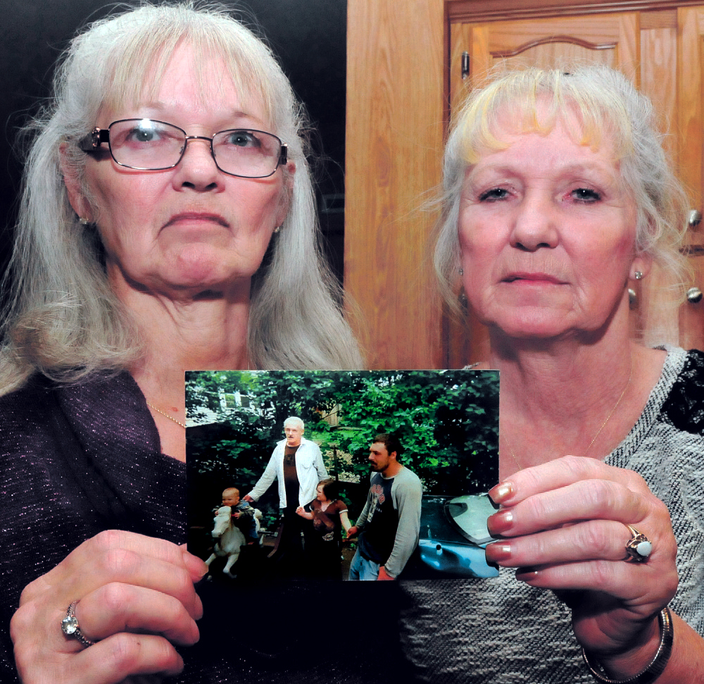 Joan Cuares, left, and Debbie Deyoung, hold a photograph that shows their brother Dana Kitchin on Dec. 18, 2014. Kitchin was found dead Dec. 12, 2014, at the Kennebec County Correctional Facility in Augusta.