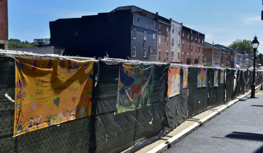 A few of the murals hanging on the fence Friday along Water Street in Hallowell.