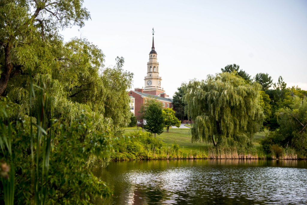 Miller Library towers over campus as it reflects in Johnson Pond at Colby College in Waterville on Saturday.