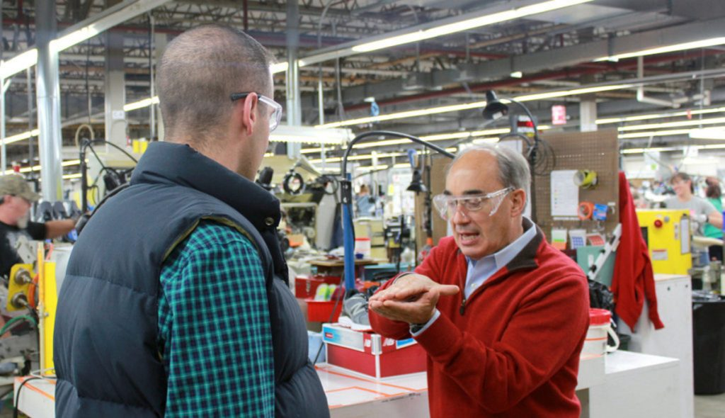 U.S. Rep. Bruce Poliquin, R-Maine, right, talks with John Alvarez, public affairs manager of New Balance, in October 2016 about the methods New Balance uses to put soles in their shoes.