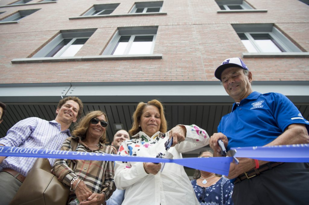 Joan Alfond, center, and Bill Alfond, right, cut the ribbon Wednesday at the Bill & Joan Alfond Main Street Commons public opening in Waterville.