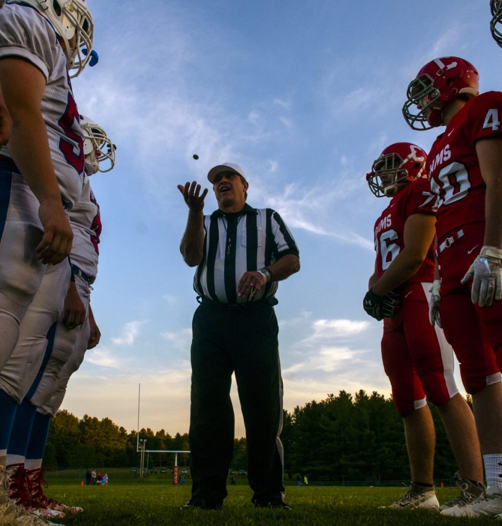 Referee Doug Gilbert, center, tosses a coin between Messalonskee, left, and Cony before their Pine Tree Conference B game last Friday in Augusta.