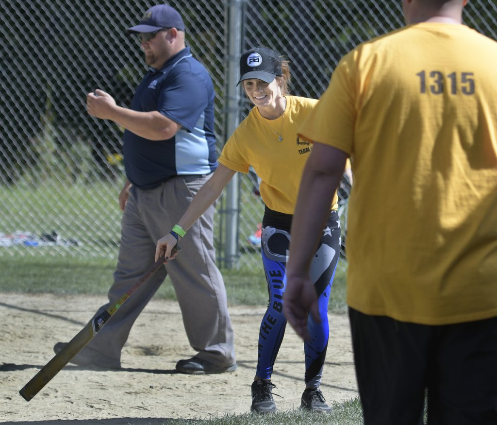 Jill Cole collects a bat Sunday after returning to home plate while playing for the Somerset County Sheriff's Department softball team at the Fraternal Order of Police tournament in Sidney. The fourth tournament was held in honor of Cole's father, Somerset Deputy Cpl. Eugene Cole, who lost his life in the line of duty April 25 in Norridgewock. The law enforcement union members fielded 12 teams, according to organizer Brittany Johnson, a detective with Kennebec County Sheriff's Office. All the money was donated to Cole's family.