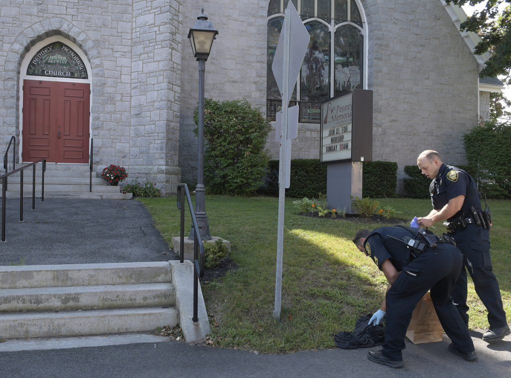 Augusta Police Department officers collect a black hooded sweatshirt Sunday in front of Penney Memorial United Baptist Church in Augusta moments after an armed robbery at a Walgreens next door.