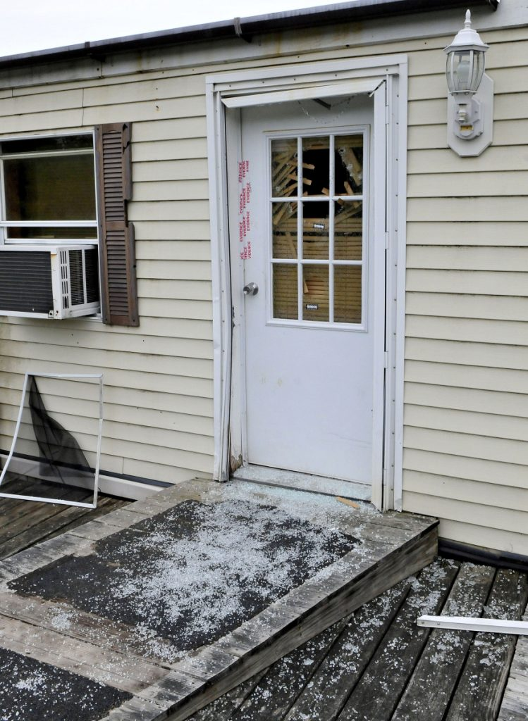 Glass from a shattered window in a door that is sealed with police evidence tape is seen at the front entrance to a mobile home at 1003 Oakland Road in Belgrade on May 22, 2017. Homeowner Roger Bubar died in a police officer-related shooting on May 19, 2017, and his son, Scott Bubar, was seriously wounded.
