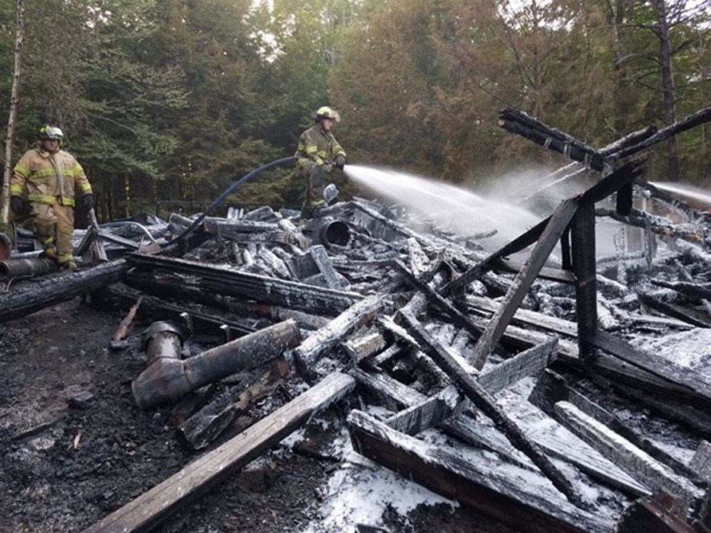 A log cabin camp on Hancock Pond in Embden that burned to the ground on Sunday, was started by a wood stove. No one was injured, but photographs of the family who has owned the camp for decades were destroyed.