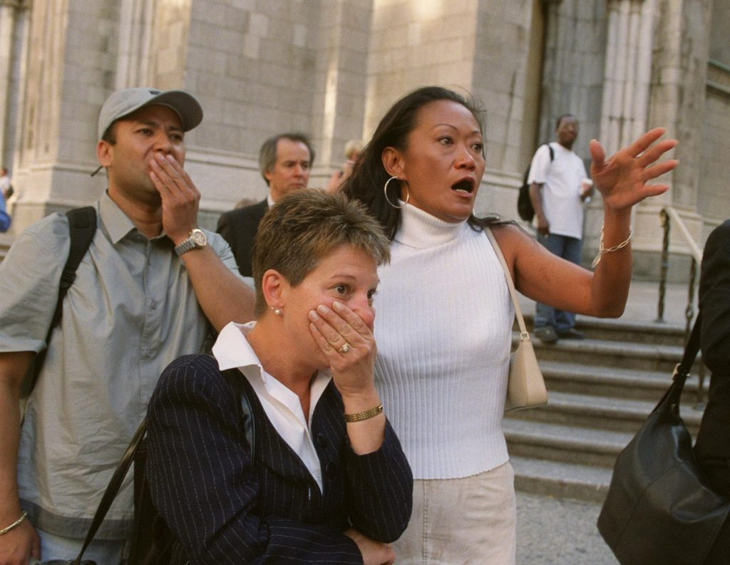 People in front of New York's St. Patrick's Cathedral react with horror as they look down Fifth Avenue towards the World Trade Center towers after planes crashed into their upper floors, in this Sept. 11, 2001 photo.