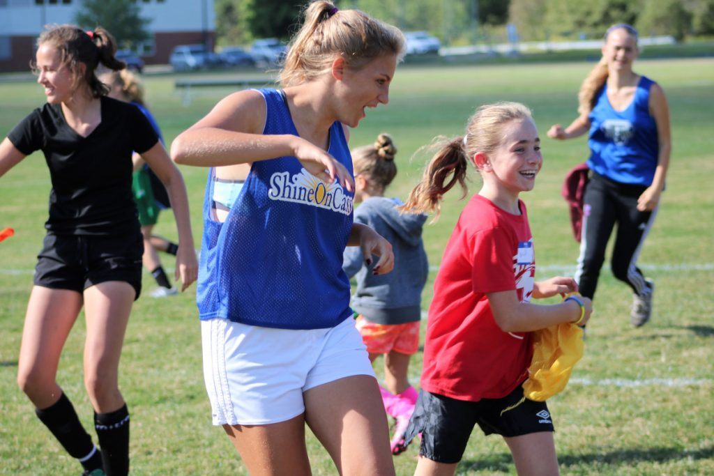 Fourth grader Brielle Dostie, right, keeps pace with Messalonskee soccer player Elena Guarino at ShineOn Saturday on Sept. 8 in Oakland. Guarino, along with her teammates Lydia D'Amico, in back on left and Molly Calkins, in back on right, and the Eagles Girls Soccer team, were part of an annual event to promote youth mentoring and share kindness in memory of former Eagle soccer player Cassidy Charette of Oakland.
