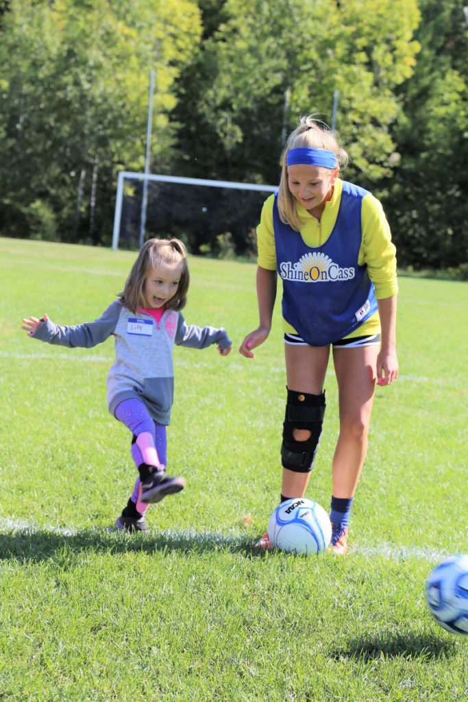 Messalonskee Girls Soccer Team player Lydia Bradfield, right, shares her foot skills with Lillyanne Dyer at ShineOn Saturday, a girls' youth mentoring day created by the ShineOnCass Foundation to honor and remember Cassidy Charette.