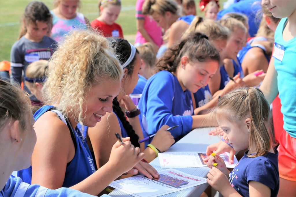 "Kylie Wolfe, right, is all smiles as she gets an autograph from Alexa Brennan, left, and other members of the Messalonskee High School Girls Soccer team at the third annual ""ShineOn Saturday"" held Sept. 8 at Messalonskee High School. The event honored the late Cassidy Charette, of Oakland, who was a youth mentor and junior midfielder for the Eagles before her passing in 2014."