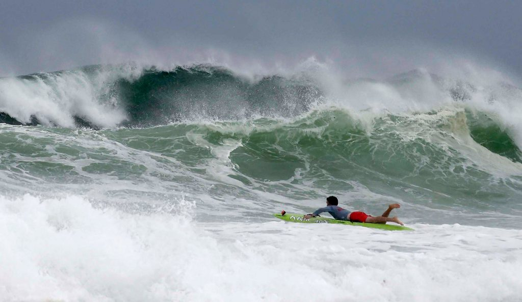 Mitchell Nugent paddles a board toward waves near Crystal Beach in Destub, Fla., on Tuesday as Tropical Storm Gordon churns the Gulf of Mexico.