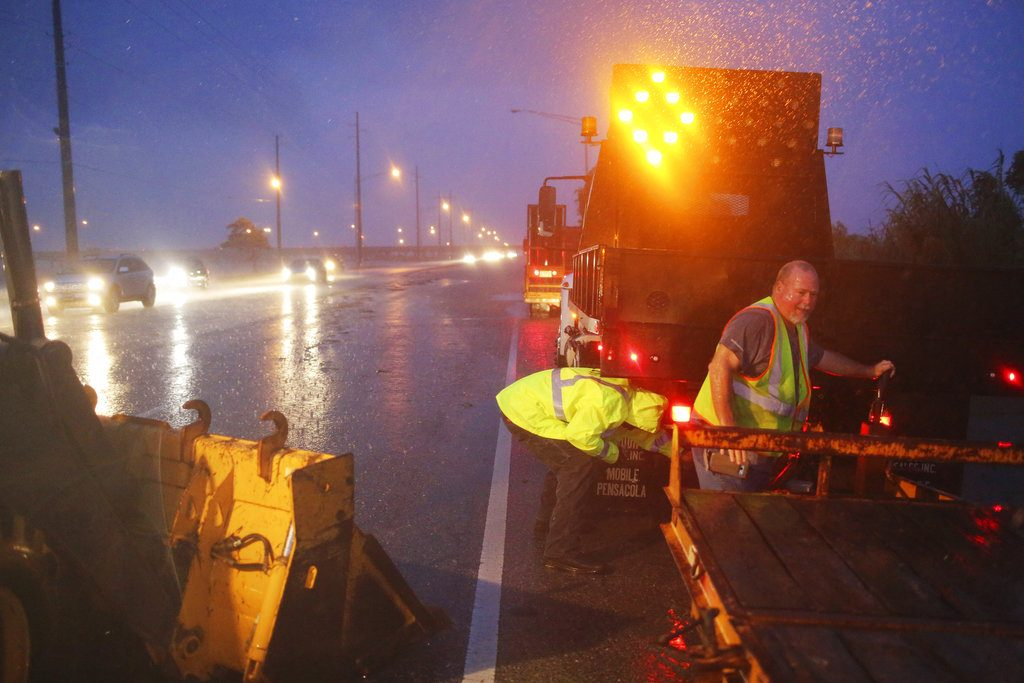 Crew members with the Alabama Department of Transportation work to block off a flooded part of US Highway 98 while fighting rain from Tropical Storm Gordon on Wednesday, in Spanish Fort, Ala.