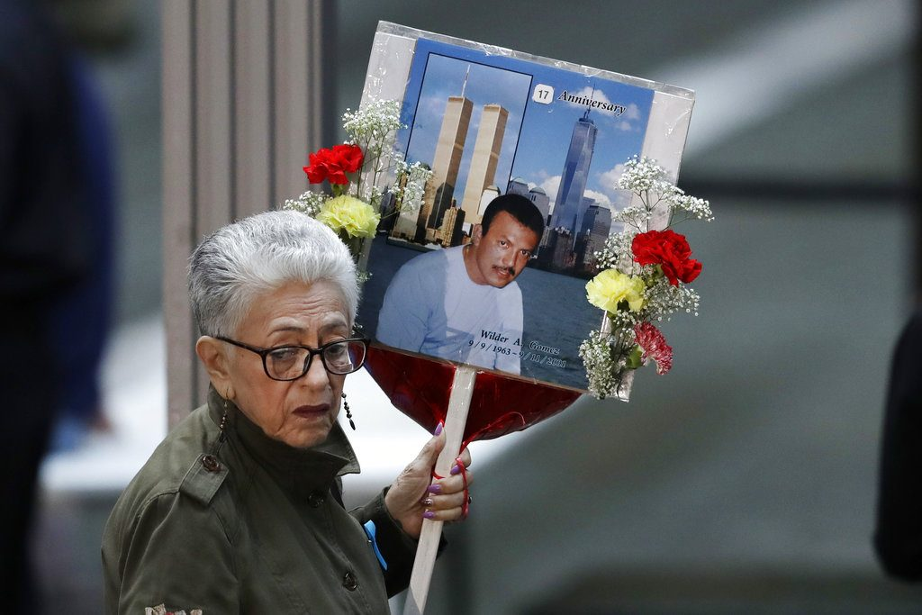 A woman arrives with a sign bearing photo memories for Wilder Gomez at the 17th anniversary of the terrorist attacks on the United States, Tuesday, Sept. 11, in New York. Gomez, from Colombia, was a bartender at Windows on the World on the 103rd floor of the World Trade Center when it was attacked.