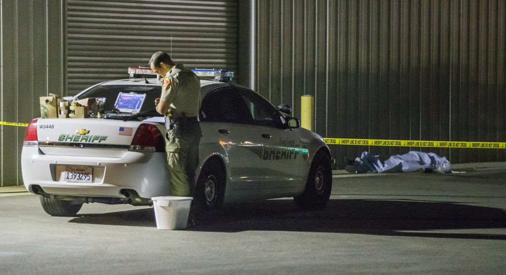 A Kern County sheriff's deputy stands near an area where a shooting victim lies, Wednesday, in Bakersfield, Calif. A gunman killed five people, including his wife, before turning the gun on himself, authorities said.