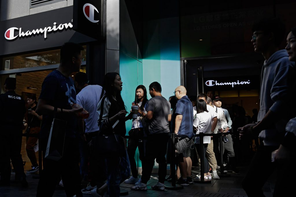 People walk by shoppers who wait in line to enter a store selling sportswear by American brand Champion, at the capital city's popular shopping mall in Beijing on Monday. China raised tariffs Monday on thousands of U.S. goods in an escalation of its fight with President Trump over technology policy, and it accused Washington of bullying Beijing and damaging the global economy.