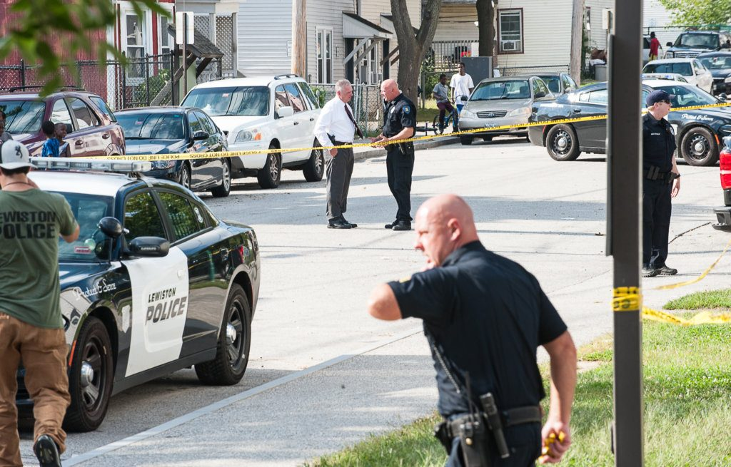 Lewiston police officers, detectives and other law enforcement officials confer Wednesday in the middle of Knox Street in Lewiston, where a man with stab wounds collapsed after running out of the nearby parking lot of a housing development.