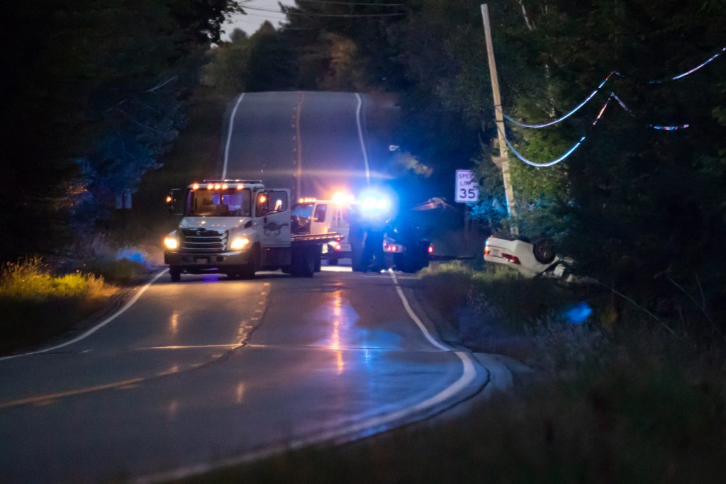 A wrecker arrives on scene and hauls the remains of a white passenger car from the woods of the Thurston Hill Rd, west of State Route 201 on Saturday evening.
