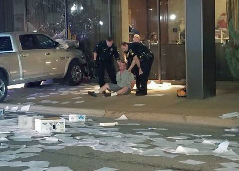 In this image taken from video by KDFW Fox 4 a man is detained after crashing his pickup truck into the side of the Fox affiliate television station building in downtown Dallas on Wednesday.