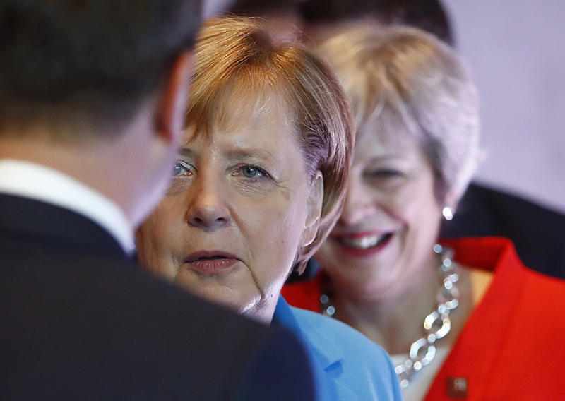 German Chancellor Angela Merkel, left, and British Prime Minister Theresa May wait for the beginning of the plenary session of the informal EU summit in Salzburg, Austria on Thursday.