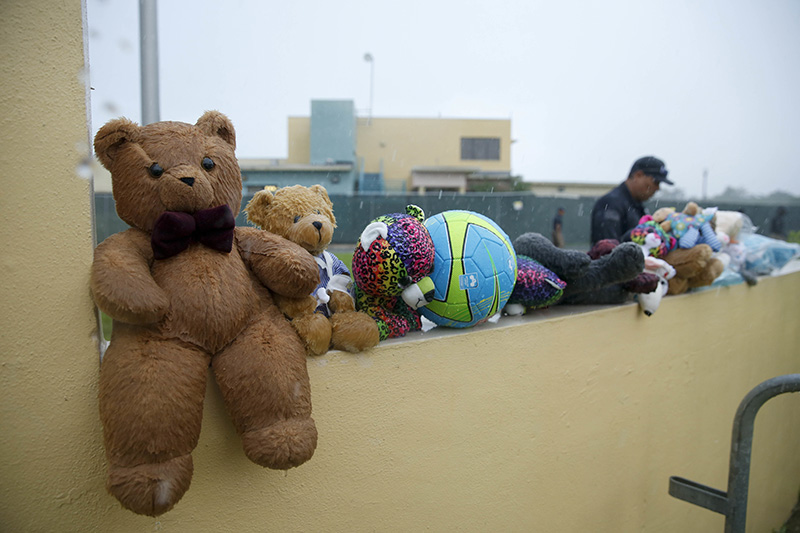 A guard walks by toys placed for the migrant children by protesters as they march to Homestead Temporary Shelter for Unaccompanied Children in Florida in June.