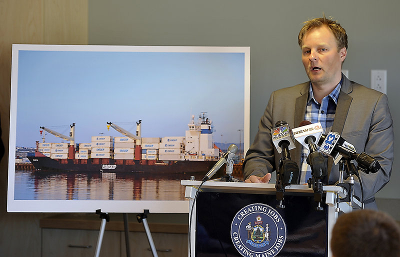 Standing with a picture of an Eimskip operation, General Manager Larus Isfeld talks to the media  about coming to Portland in 2014. He is leaving the company.