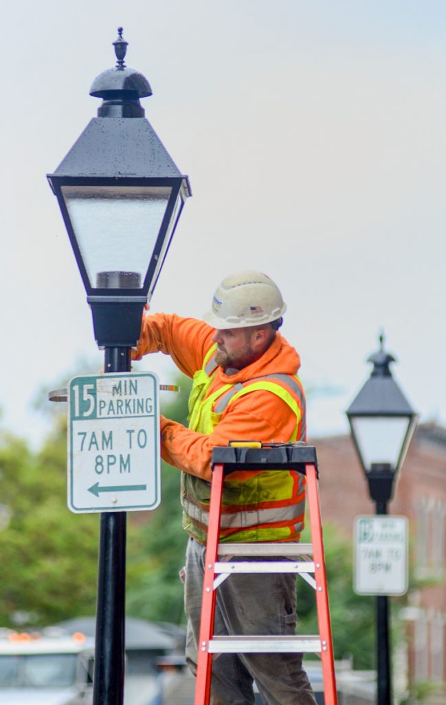 Dan Clark, of Sargent Corporation, installs 15 minute parking signs on new lamp posts on Tuesday on Water Street in downtown Hallowell. The road will open to two-way traffic again on Friday afternoon after a months-long reconstruction project.
