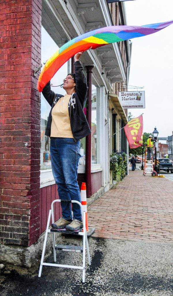 Standing on a stepladder, Malley Weber hangs a flag outside of her shop, Hallowell Clay Works, on Tuesday on Water Street in downtown Hallowell. She said that when workers finish installing the new brick sidewalks at the corner of Water and Union streets she should be able to reach the flag mount without a stepladder again.