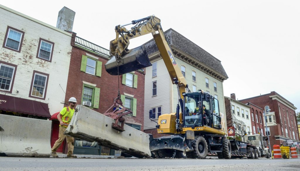 Construction workers remove Jersey barriers from the middle of Water Street on Tuesday in downtown Hallowell.