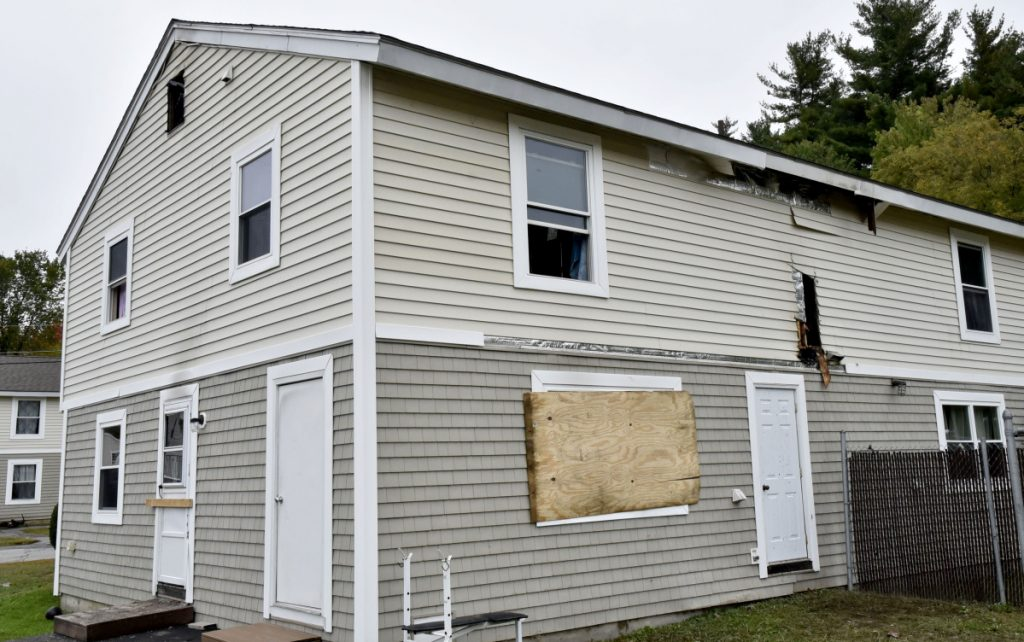 Windows have been boarded up and blackened holes were left from a grease fire that damaged this home at 16 Crawford St. in Waterville on Tuesday.
