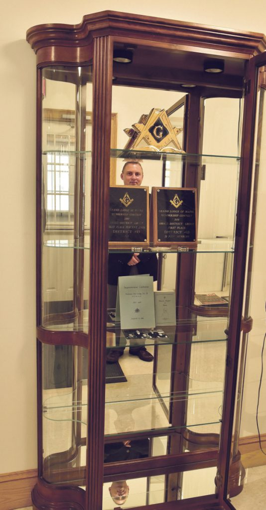 Mason Brian Nelson is reflected in a display filled with historic items of Northern Star Lodge 28 on Thursday in North Anson, The Masons plan to celebrate the lodge's bicentennial on Saturday with a barbecue, music, vendors and entertainment.