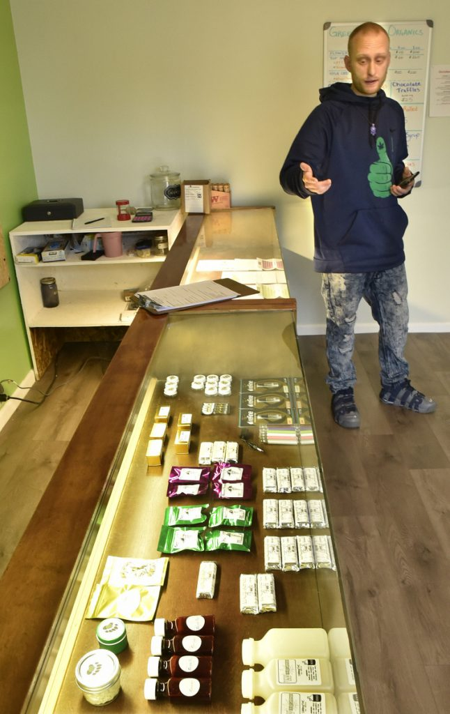 Green Thumb Organics shop owner Dan Hall looks over a display case filled with edible medical marijuana products on Thursday.