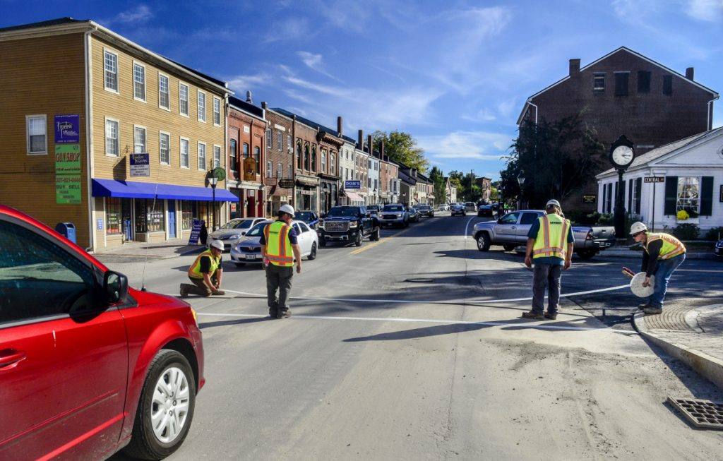 Workers put reflective tape in the crosswalk on Friday at corner of Central and Water Streets in downtown Hallowell. Traffic is flowing in both directions again after both lanes were reopened just before 3 p.m.