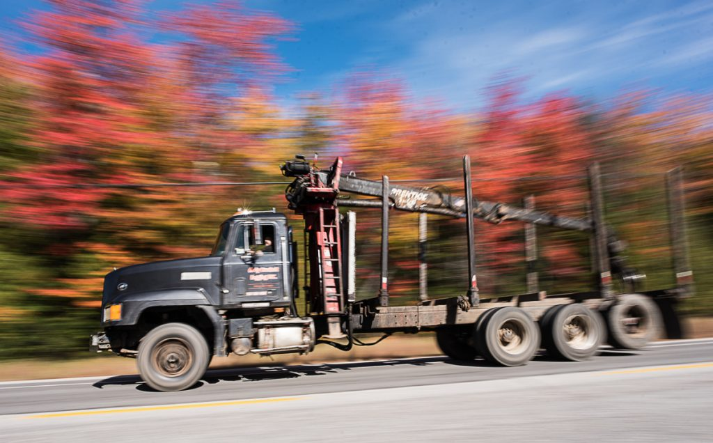 An empty logging truck zooms past a large display of autumn foliage Friday afternoon on Route 26 in Woodstock.