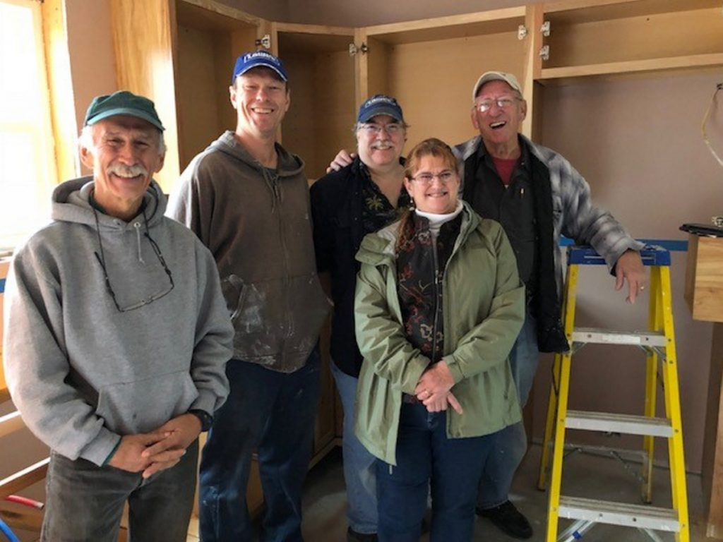 Habitat for Humanity volunteers Mike Grant, Dan Patterson, Dean Dolham and Roland Rancourt stand with Habitat for Humanity & Re-Store Waterville Area executive director Linda Santerre at a house they are building on Clark Street in Waterville.