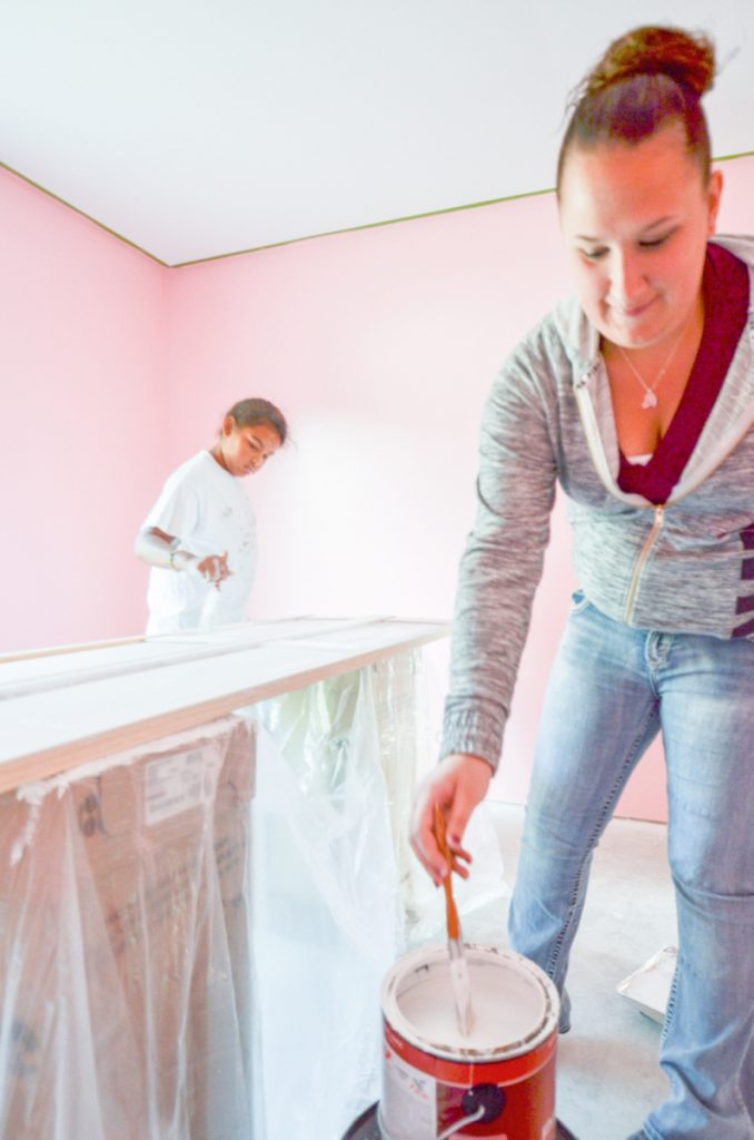 Alyssa Bofia, 10, of Waterville, left, helps Maggie Lebrun of Waterville paint closet doors at a new Waterville Area Habitat for Humanity house on Clark Street recently. Lebrun is the new owner and plans on moving in with her two children this fall.