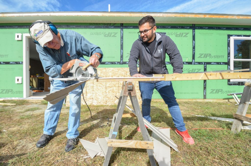 Roland Rancourt, left, of Shawmut, and Mert Ozsaydi, of Waterville, measure and cut siding recently for installation on a house being built by Waterville Area Habitat for Humanity.