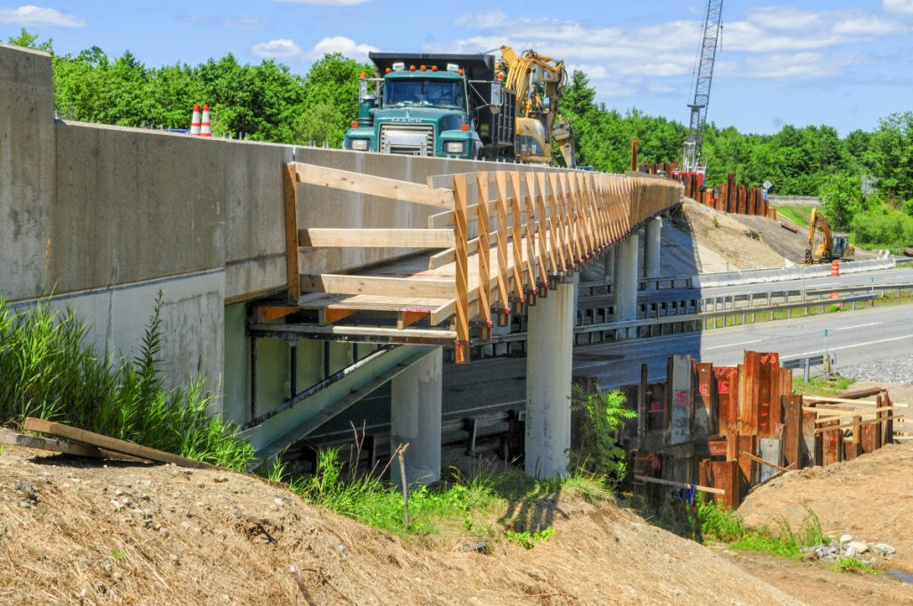 Wyman & Simpson employees work on the project to re-deck a bridge that carries the Interstate 95 exit 103 southbound traffic over Interstate 295 to the toll booth on July 18 in West Gardiner.