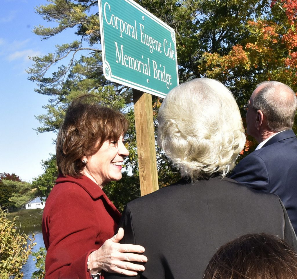 "U.S. Sen. Susan Collins, R-Maine, left, reaches out to Sheryl Cole, widow of slain Somerset Sheriff Deputy Cpl. Gene Cole, after a sign was unveiled during the dedication of the Corporal Eugene Cole Memorial Bridge in Norridgewock on Sunday. Collins later said had been hearing ""very positive"" feedback from Mainers regarding her vote the day before to confirm now-Supreme Court Justice Brett Kavanaugh."
