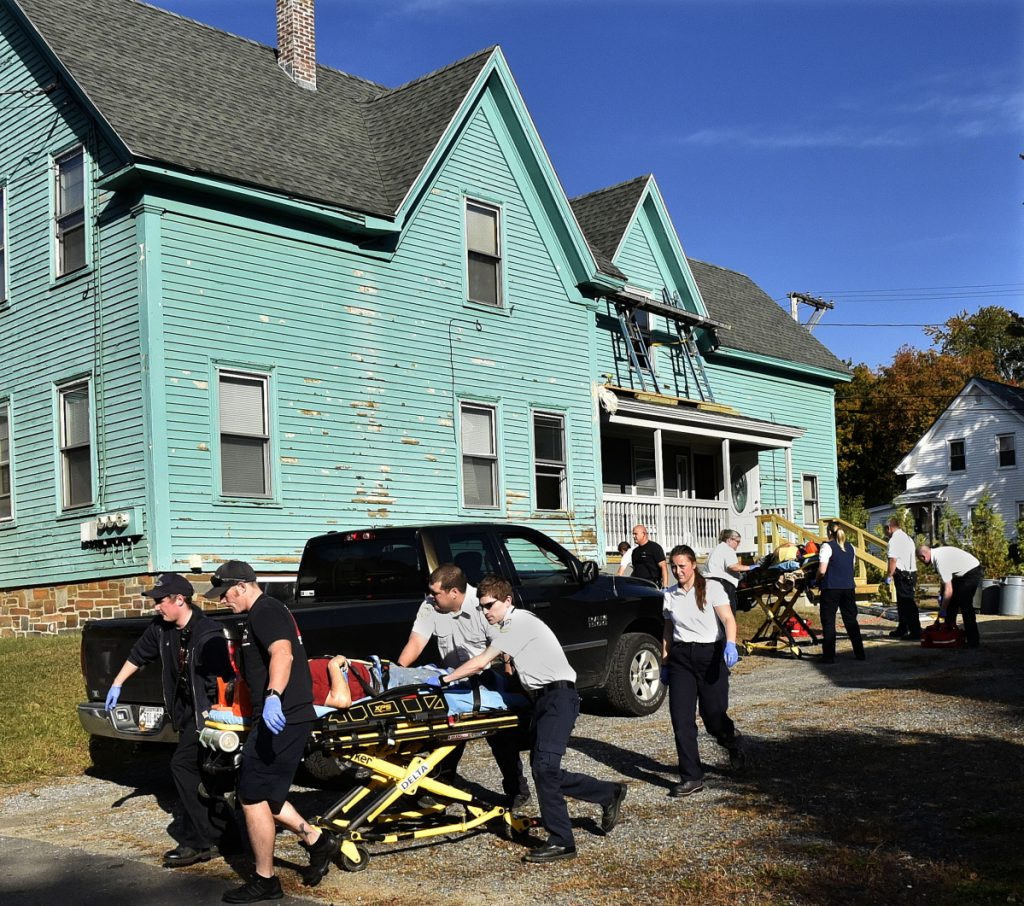 Two men are transported on gurneys by rescue personnel to the hospital after falling from scaffolding, background, while working on a home on Brook Street in Waterville on Wednesday morning.