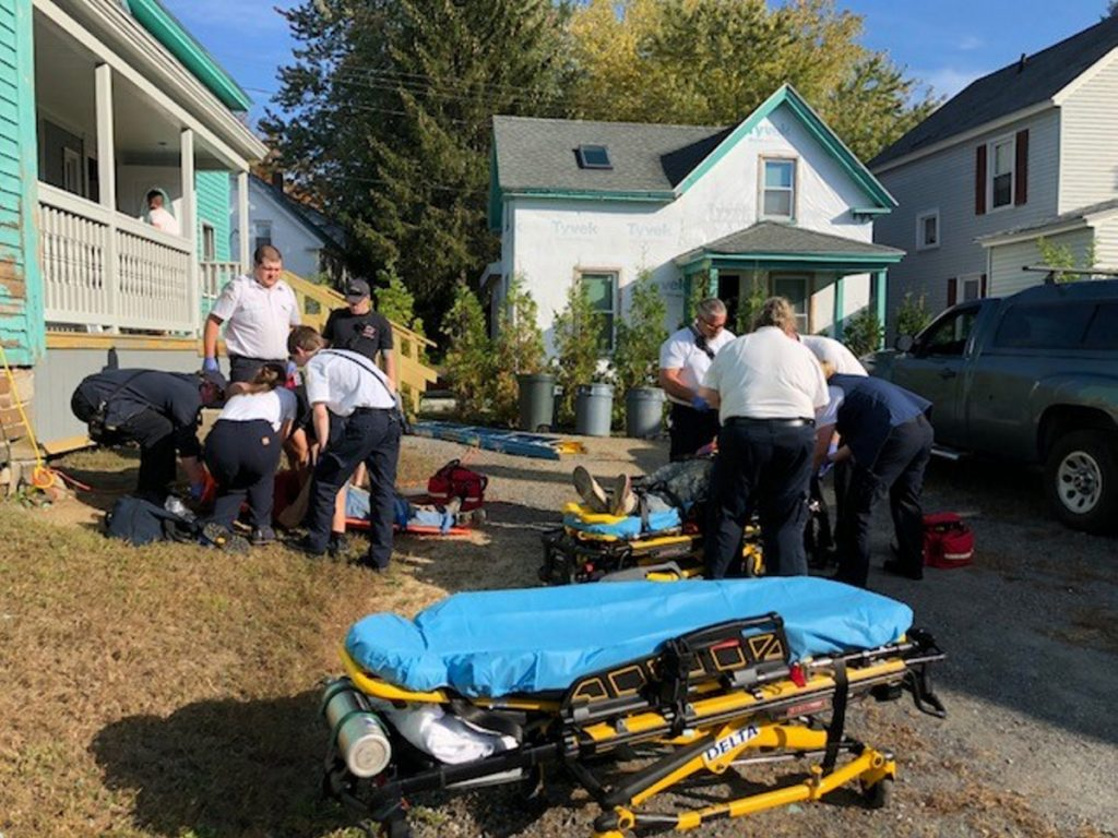 Emergency responders attend to two men who reportedly fell off roof scaffolding Wednesday morning in Waterville.