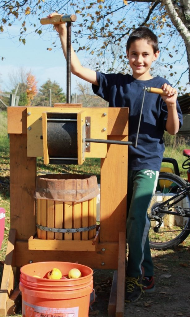 Keiran Roopchand turning the cider press at Pumpkin Vine Family Farm in Somerville.