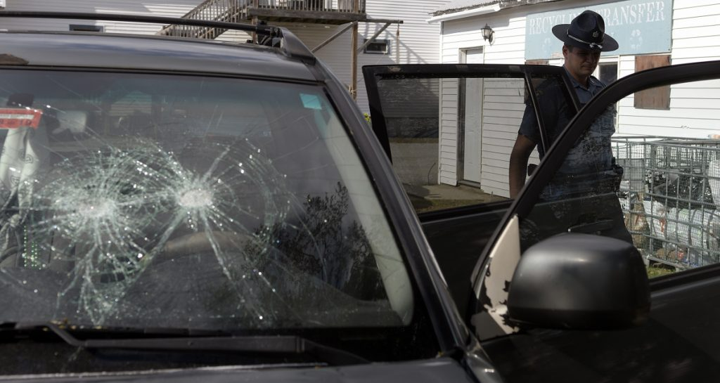 State Trooper Jim Moore examines an SUV that had its windshield smashed in the parking lot of the Litchfield Country Store Wednesday. Troopers are working with the Office of State Fire Marshal to determine the origin of a fire that was ignited in the car. Firefighters from Litchfield were called to the scene. No injuries were reported, according to police.