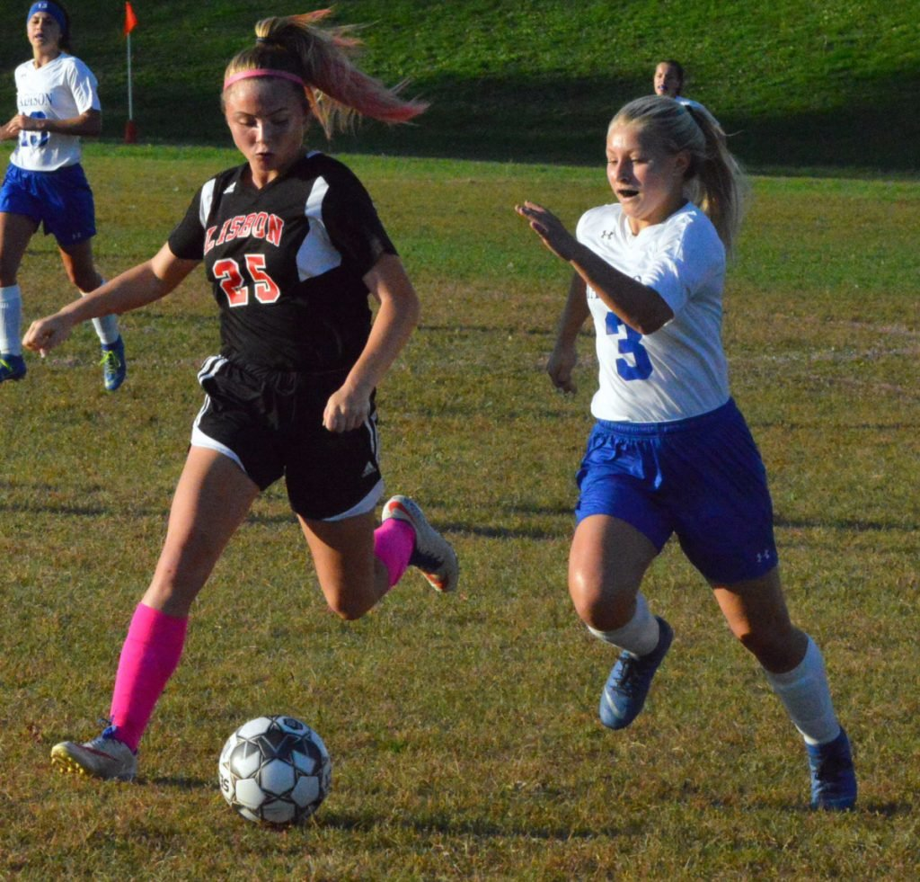 Madison's Taylor Tillinghast races down the field to the ball as Lisbon's Caitlyn Hall pursues during a game Wednesday in Lisbon.